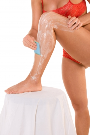 Body hygiene: Woman depilates scrubs hair removal cream off her leg photo