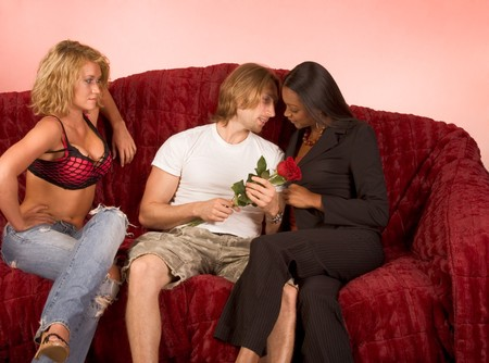 Young beautiful ethnic woman tries to seduce young Caucasian man holding red rose while his girlfriend disapprovingly observes the scene. Group sits on couch covered by red blanket. Ethnic woman wears business clothes, while others are in very casual outf photo