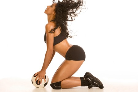 Fitness series sexy mid aged female couch in sport clothes, standing on her knees holding black and white football ball, with her hair flying photo