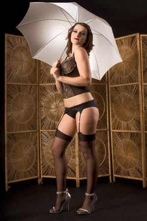 Retrato de joven mujer sensual estilo retro en maquillaje y vestuario (ropa interior, medias altas negro muslo y buhardilla cinturón) la celebración de paraguas de color blanco Foto de archivo - 4191197