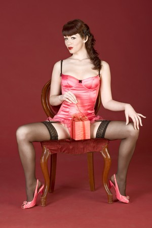 Sexy pinup girl with spread legs surprised by her Valentine Day or birthday present. She sit on red chair and unwrap the gift box
