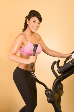 athleticism: Young woman sweaty while working out on elliptical machine