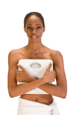 African American topless woman with her hips wrapped in bath towel covers her chest with weighscales confident in her success with weight control dieting strategy results Stock Photo - 4191157