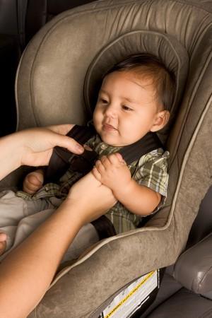 Lachend biracial Aziatische Filipijnse jongen zitten in de auto zitten terwijl de ouders de handen gesp hem Stockfoto - 4191196