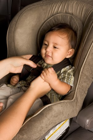 car seat: Smiling biracial Asian Filipino kid sitting in car seat while parent hands buckle him up
