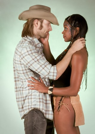 mixed race couple: Loving mixed race couple - Caucasian male in cowboy clothes and hat, and ethnic young beautiful woman in Pocahontas outfit