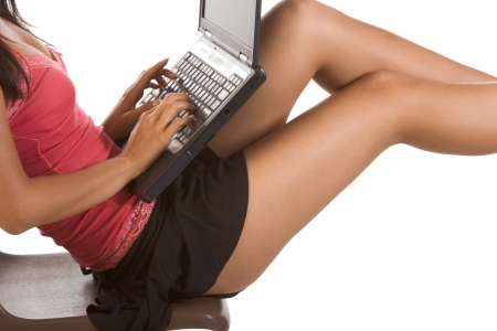 Perfectly shaped legs, hips, and torso of unrecognizable female student sitting on the desk with notebook portable PC on her lap. She is typing on this computer keyboard Stock Photo - 4191181