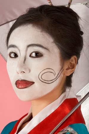red skinned: Asian female with geisha style face paint in yukata (kimono) with umbrella Stock Photo
