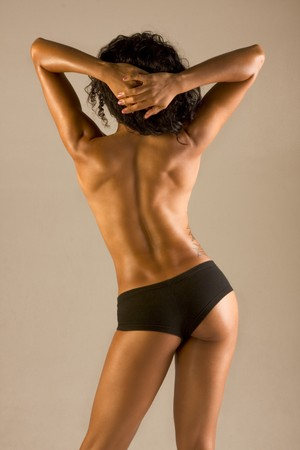 Very fit, muscular athletically built topless woman standing with her back towards to camera 免版税图像 - 4243390