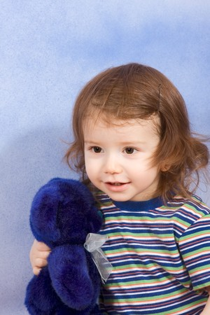 two persons only: Portrait of kid holding blue Teddy bear (blue background)