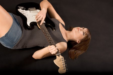 Guitarist - Young woman in tank top and shorts laying down on her back with electric bass guitar and playing on it photo