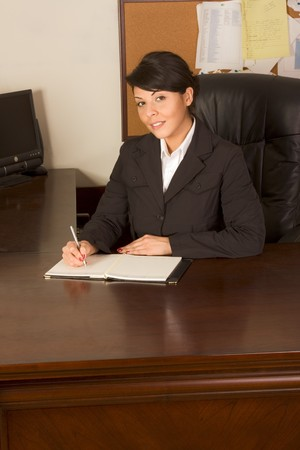 dayplanner: Businesswoman sitting by desk in her office and writing down her schedule in day planner