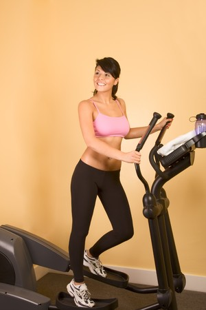 elliptical: Young woman in sporty outfit sweaty while working out on elliptical machine