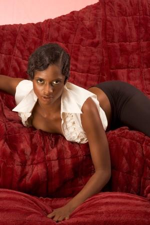 Glamorous retro style (20s) dark skinned sensual female lying down on red sofa Stock Photo - 4259231