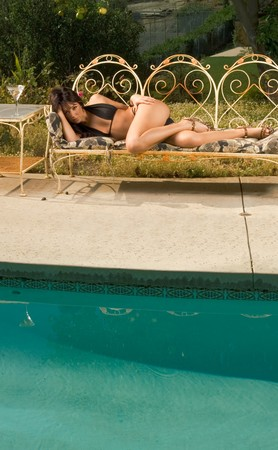 Young sensual woman in black bikini lying down on iron garden bench outdoors by swimming pool, sunbathing, with cocktail glass on table by her side photo