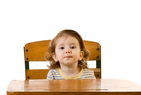 grimacing: Early development series - Grimacing funny looking baby boy sitting at school desk