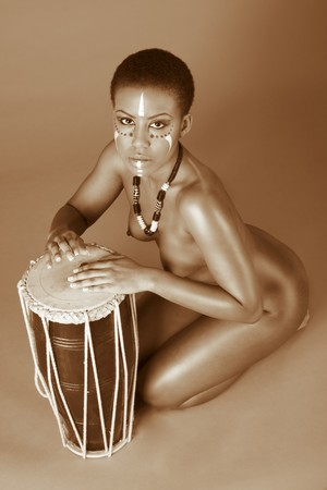 naked african: Portrait of African American woman wearing original tribal themed face-paint and necklace playing Conga drum (toned) Stock Photo