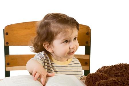 早い開発シリーズ - それについての本とおもちゃで学校の机に座って思慮深く探究表情と男の赤ちゃん。彼はいくつかの人とどうやら教科書を彼の