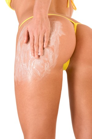 female putting moisturizer on her hips, thigh and buttocks(close up) photo