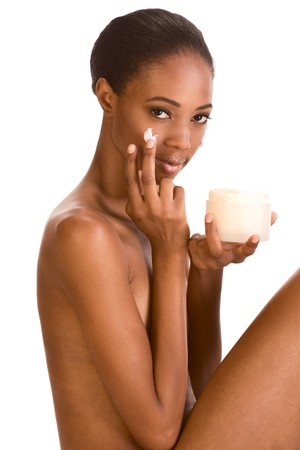 Beautiful nude young African American woman with Slicked Back Hair applying moisturizer on her face Stock Photo