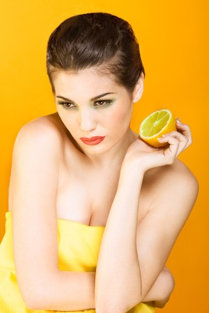 Gorgeous young woman wearing colorful make-up and holding half of lemon, on yellow background photo