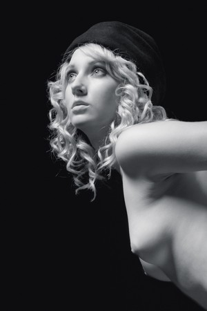 Nude beautiful blond with curly hair and developed firm breast wearing hat, standing and bending forward
