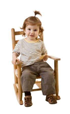 baby on chair: Head and shoulders image of funny looking baby boy with long hair sitting in baby chair and holding cracker