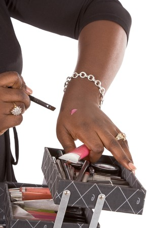africanamerican: African-American makeup instructor prepare make-up component and check for proper color putting it on her hand (close up)