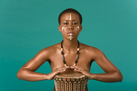 Portrait of African American woman wearing original tribal themed face-paint and necklace playing Conga drum Stock Photo - 4389838