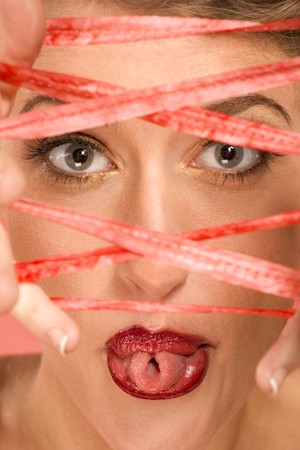 Portrait of beautiful woman wearing dramatic makeup, sticking out her tongue and rolling it into tube shape, looking through rope stretched over her fingers photo