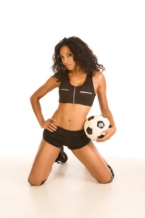 Fitness series �C sexy mid aged female couch in sport clothes holding black and white football ball photo
