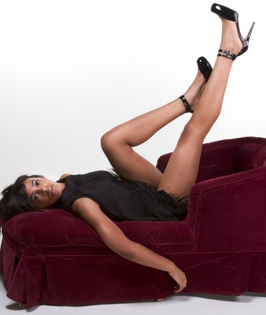 sofa: Portrait of a beautiful black glamour African American female in black dress lying down on red sofa with legs up in air Stock Photo
