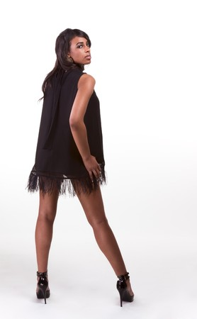 Portrait of a beautiful black African American female with long legs in black dress photo