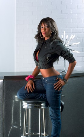 Young ethnic black Afro American in jeans female standing by bar countertop table with one leg on stool 스톡 콘텐츠