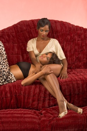 Two dark skinned sensual female lovers petting on couch (retro style) photo