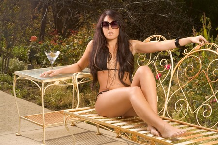 Young sensual woman in black bikini sitting on iron garden bench outdoors sunbathing, with cocktail glass on table by her side. Stock Photo