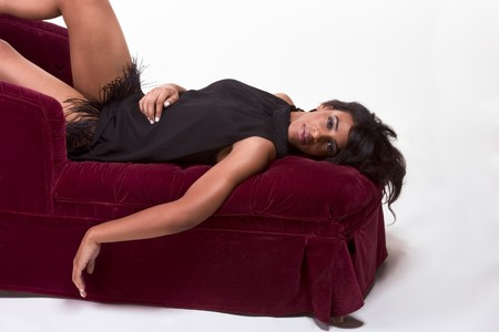 Portrait of a beautiful black glamour African American female in black dress lying down on red sofa photo