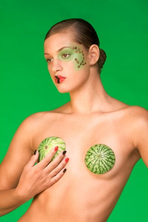 Young woman with dramatic extravagant make-up wears bra made of watermelon peel photo