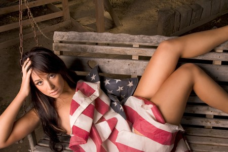 Young woman lying down on outdoors garden bench. She wear no clothes and is covered by American flag Stock Photo