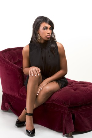 attractiveness: Portrait of a beautiful black glamour African American female in black dress sitting on red sofa