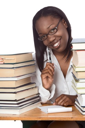 African-American ethnic black young female student in eyeglasses with pen and notepad sitting at school desk by piles of books Banque d'images