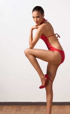 Young slender female fashion model of mixed Creole and African-American ethnicity in monokini standing on one leg photo