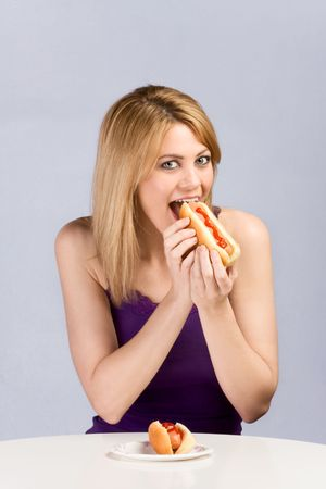 Beautiful blonde female biting hot dog bun with sausage and ketchup during lunch break. The second helping is in front of her on table placed paper plate. photo