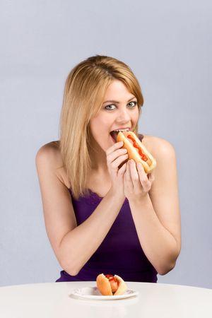 perro caliente: Hermosa rubia femenina mordiendo pan de perro caliente con salchicha y salsa de tomate durante almuerzo. La segunda es ayudar en el frente de su papel en el cuadro colocado la placa.