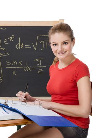 square root: High school or college female student sitting by the desk at math class. Blackboard with advanced mathematical formals is visible in background