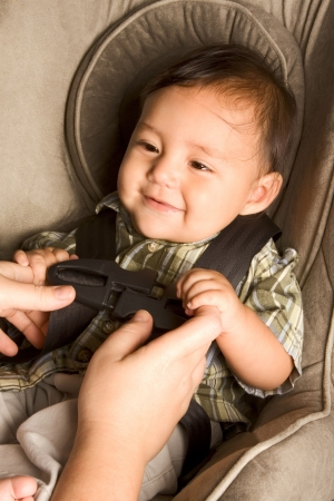 Smiling biracial Asian Filipino kid sitting in car seat while parent hands buckle him up