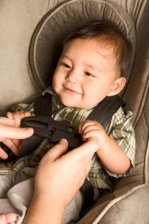 asiento coche: Sonriendo birracial Asia filipino chico sentado en asiento del coche mientras que los padres le hebilla manos hasta Foto de archivo