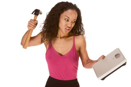 underweight: Young female hits weight scales by hammer Stock Photo
