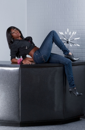 Young ethnic black Afro American in jeans female sitting and leaning on bar countertop table  Archivio Fotografico