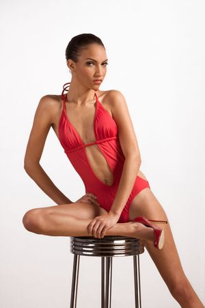 Young slender female fashion model of mixed Creole and African-American ethnicity in monokini sitting on stool with one leg stretched out and holding ankle by another hand